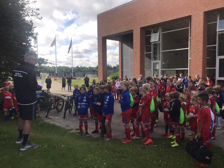 I højt solskin har 128 glade drenge og piger netop taget hul på årets fodboldskole på NMT-Byens Arena.